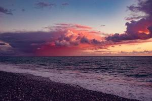Seascape of beach and body of water with a colorful cloudy sunset