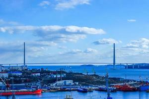 Paisaje urbano de un puerto y el puente ruso con un nublado cielo azul en Vladivostok, Rusia foto