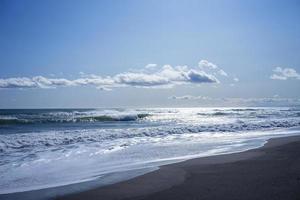 Paisaje marino de una playa y cuerpo de agua con nublado cielo azul en Kamchatka, Rusia