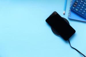 carga de teléfono inteligente sobre fondo azul foto