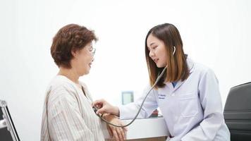 jovem médico usando um estetoscópio para examinar o coração do paciente idoso