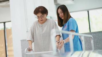 jonge fysiotherapeut helpt een senior patiënt met rollator tijdens revalidatie