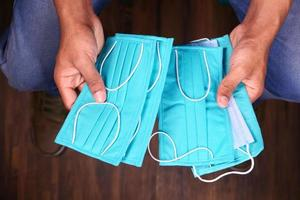manos de hombre sosteniendo mascarillas quirúrgicas foto