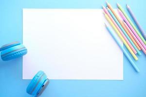 Lápices de colores con papel en blanco sobre fondo azul.