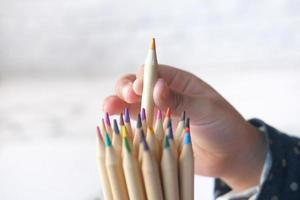 Child girl picking a colored pencil from a box photo