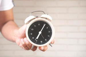 Person holding alarm clock on neutral background photo