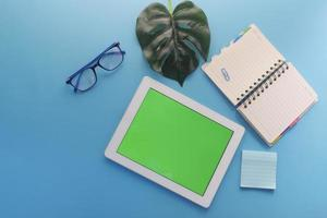 Vista superior de la tableta digital con material de oficina sobre fondo azul. foto