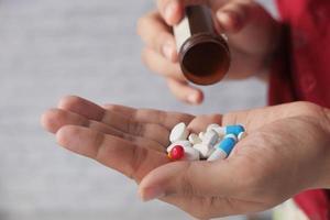 Cerca de la mano de la mujer tomando pastillas