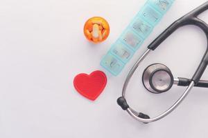 Contenedor de caja de pastillas con estetoscopio sobre fondo blanco. foto