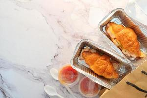 Two croissant sandwiches in takeout containers photo