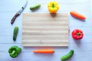Selección de alimentos saludables con verduras frescas y tabla de cortar en la mesa foto