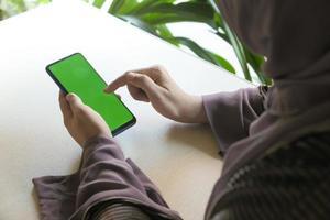 mujer usando un teléfono inteligente con pantalla verde