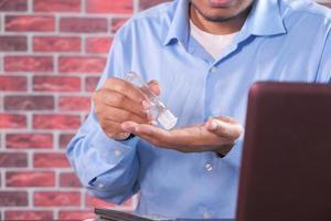empresario usando gel desinfectante foto