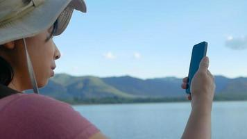 Young Female Tourists Talking to Someone on Her Smartphone Over Beautiful Mountains and A Lake