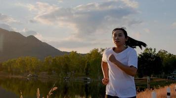 uma mulher asiática correndo na estrada à beira do lago durante o pôr do sol