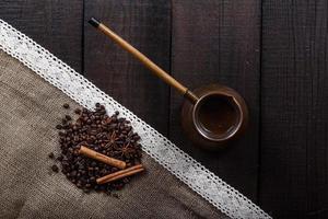 Black coffee with grains and cinnamon photo