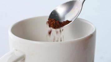 Close-up de cacao en polvo cayendo de una cuchara en una taza blanca