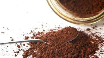 Kakaopulver, das über einen Löffel auf einem weißen Hintergrund fällt