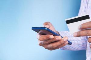 sosteniendo una tarjeta de crédito y un teléfono inteligente para comprar en línea