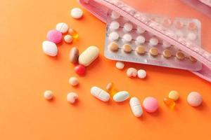 Pastillas anticonceptivas sobre fondo naranja foto