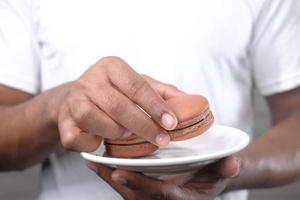 Hand picking chocolate color macaroon from a plate photo