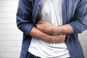 Man suffering stomach pain close up photo