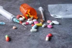 jeringas y pastillas sobre fondo gris