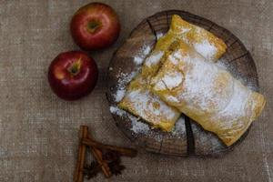 Apple strudel on wooden end of a tree with apples, cinnamon and star anise photo