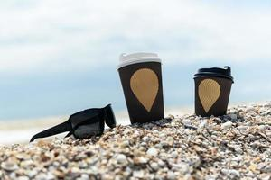 Coffee cups and glasses on the seashore photo