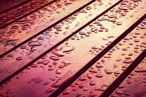 Drops of water on red wood photo