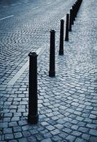 Iron pillars on pavement photo