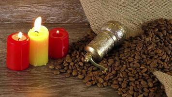 velas ao lado de grãos de café torrados e um moedor decorativo