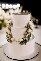 Wedding white cake on a high stand near the white podium photo