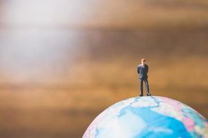 Miniature businessman standing on a globe world map with a brown background