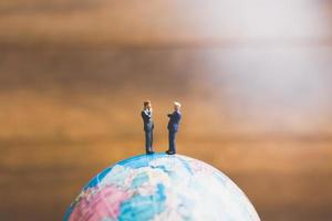 Miniature businessmen standing on a globe world map with a brown background