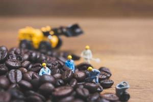 Gente en miniatura trabajando en granos de café tostados. foto