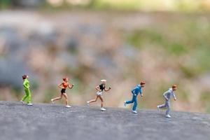 Gente en miniatura corriendo sobre una roca, concepto de salud y estilo de vida foto