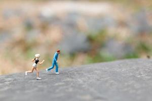 Miniature people running on a rock, health and lifestyle concept photo
