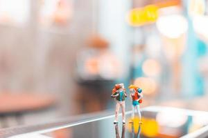 Miniature backpacker tourist people standing on a smartphone, travel concept