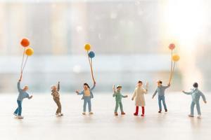 Gente en miniatura caminando con globos, concepto de familia feliz foto