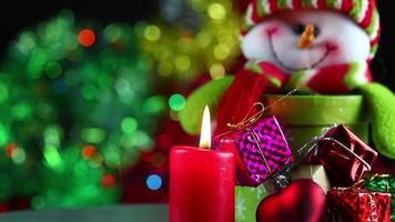 muñeco de nieve con regalos y una vela roja. video