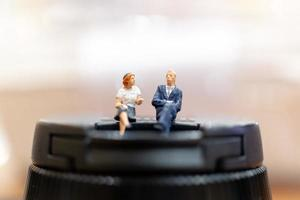 Miniature businesspeople sitting with a colorful bokeh background photo