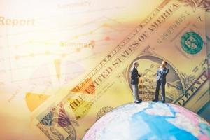 Miniature businessmen standing on a globe world map with a graph and banknotes in the background