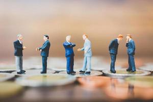Miniature businesspeople standing on money with a wooden background