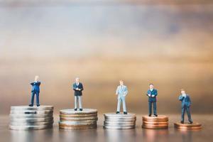 Empresarios en miniatura de pie sobre el dinero con un fondo de madera foto