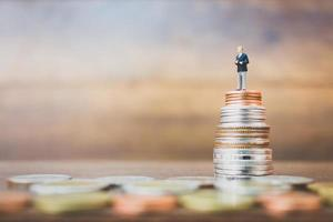 Miniature businessman standing on money with a wooden background photo