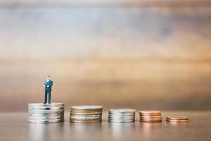 Miniature businessman standing on money with a wooden background