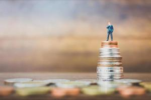 Miniature businesspeople standing on money with a wooden background photo