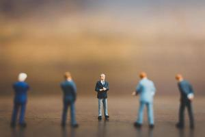 Miniature businesspeople standing on a wooden background photo