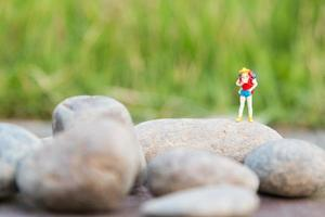 Miniature traveler with a backpack standing and walking in a meadow